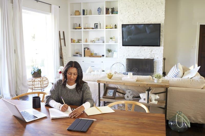 Femme d'Afro-américain âgée par milieu heureux s'asseyant à la table dans sa salle à manger faisant des notes, vue élevée photo stock