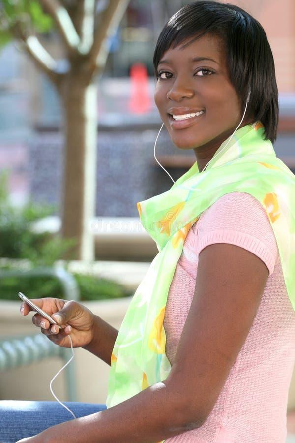 Femme d'Afro-américain écoutant la musique à l'extérieur image libre de droits