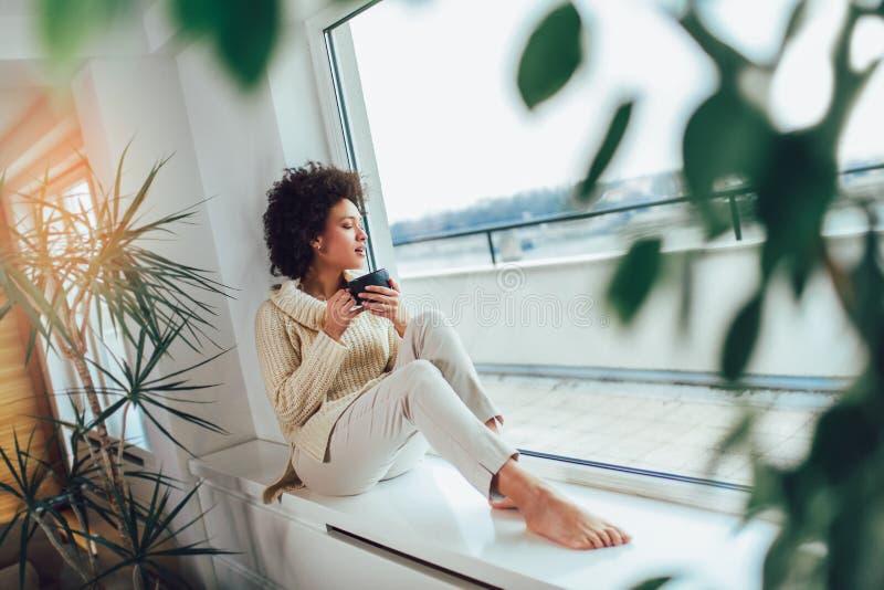 Femme d'afro-américain dans son salon buvant tenant une tasse de café photographie stock libre de droits