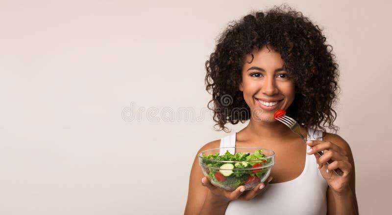 Femme d'afro-américain mangeant de la salade végétale au-dessus du fond clair photos stock