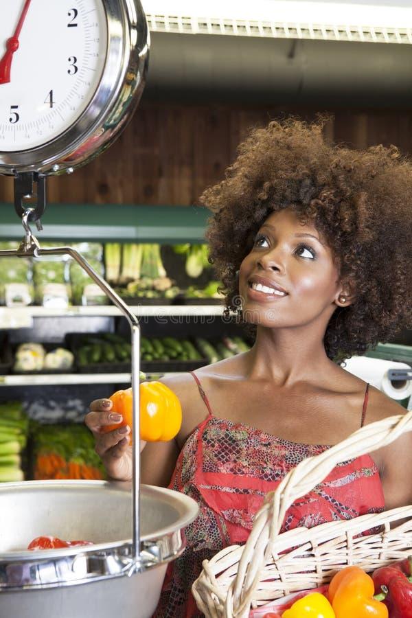 Femme d'Afro-américain pesant des paprikas sur l'échelle au supermarché images libres de droits