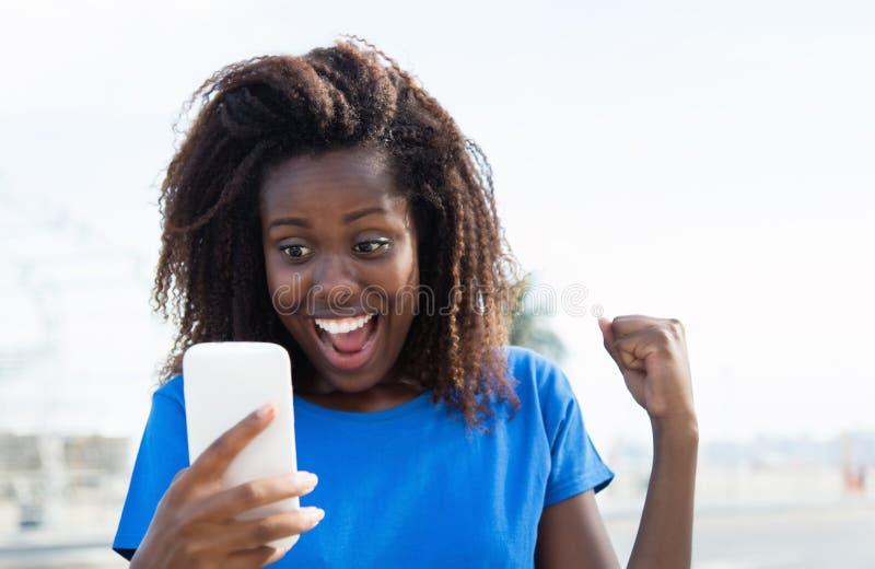 Femme d'afro-américain recevant de bonnes actualités par le téléphone photo stock