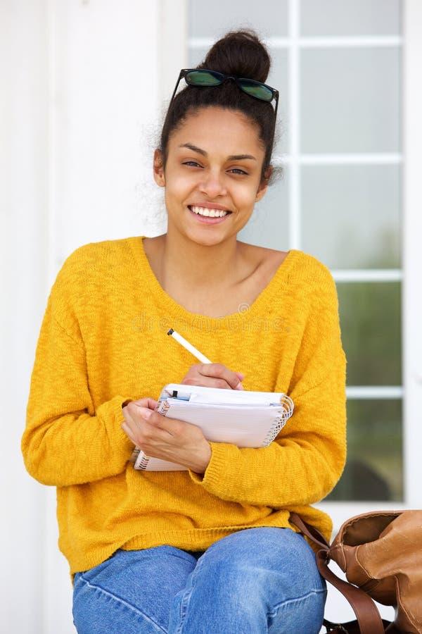 Femme d'afro-américain s'asseyant en dehors de l'écriture dans le livre photographie stock