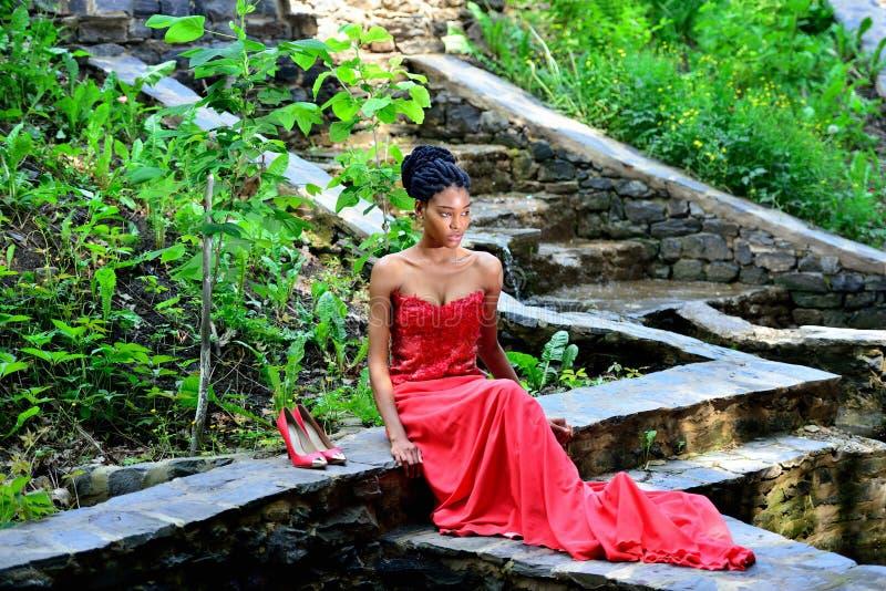 Femme d'afro-américain s'asseyant en parc posant contre le contexte des plantes vertes sur les roches dans une robe rouge avec de photos libres de droits