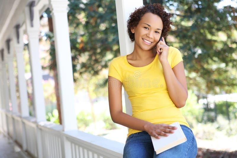 Femme d'Afro-américain sur le porche au téléphone photos stock