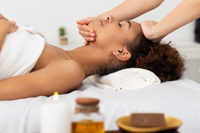 Femme d'Afro appréciant le massage de visage, détendant dans le salon de station thermale photos libres de droits