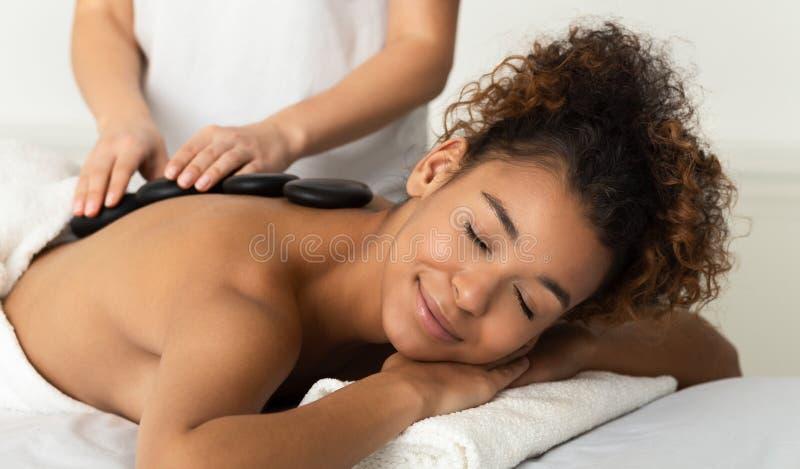 Femme d'Afro appréciant le massage en pierre chaud, détendant dans la station thermale photographie stock
