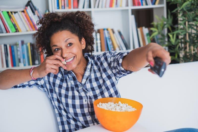 Femme d'Afro s'asseyant à la maison avec la TV de observation à télécommande images libres de droits