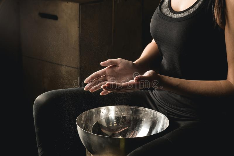 Femme d'applaudissement de mains de carbonate de magnésium de craie de gymnase photo stock
