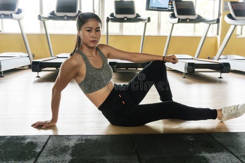 Femme d'Asiatiques dans le gymnase pour avoir un repos photographie stock