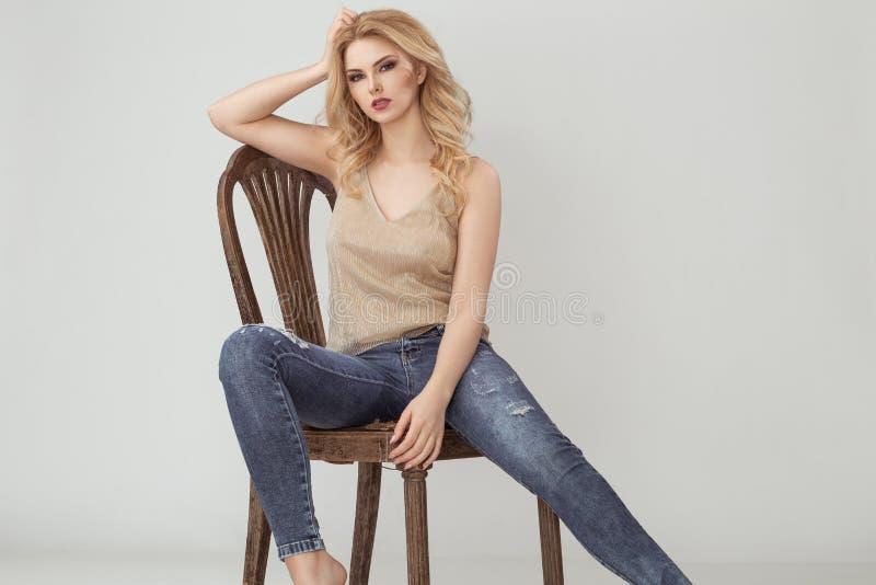 Femme d'Atractive dans la chemise d'or se reposant sur la chaise brune image libre de droits