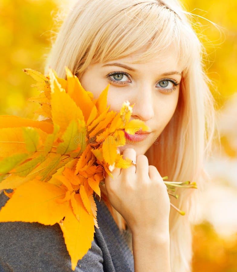 Femme d'automne avec les lames jaunes d'érable d'automne photo stock