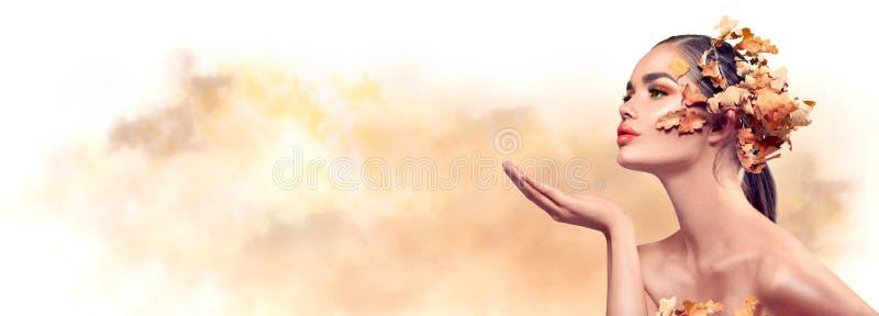 Femme d'automne. Chute. Belle mannequin fille aux feuilles lumineuses d'automne coiffure. Belle fille pointant la main, proposant  photos libres de droits