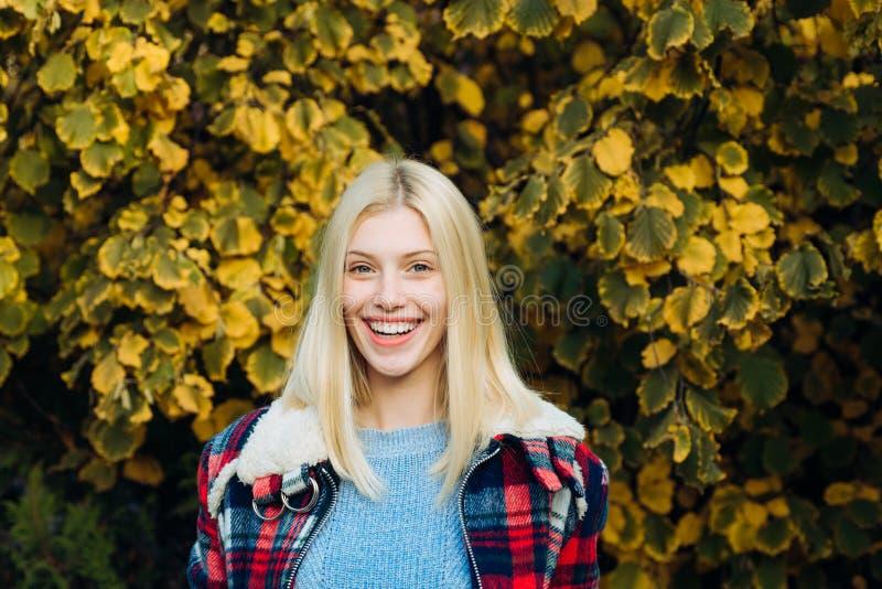 Femme d'automne Concept doux de Hugge dans des vêtements Jeune femme de sourire en stationnement Arbres avec les feuilles jaunes  photos libres de droits
