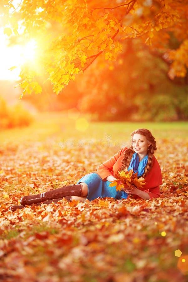 Femme d'automne sur des feuilles de paysage de chute de fond des arbres Fille photo stock