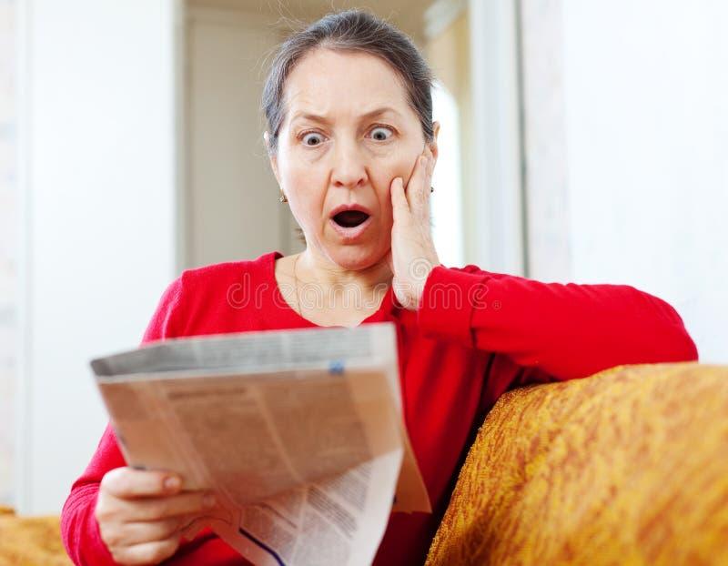 Femme d'effroi avec le journal photographie stock libre de droits
