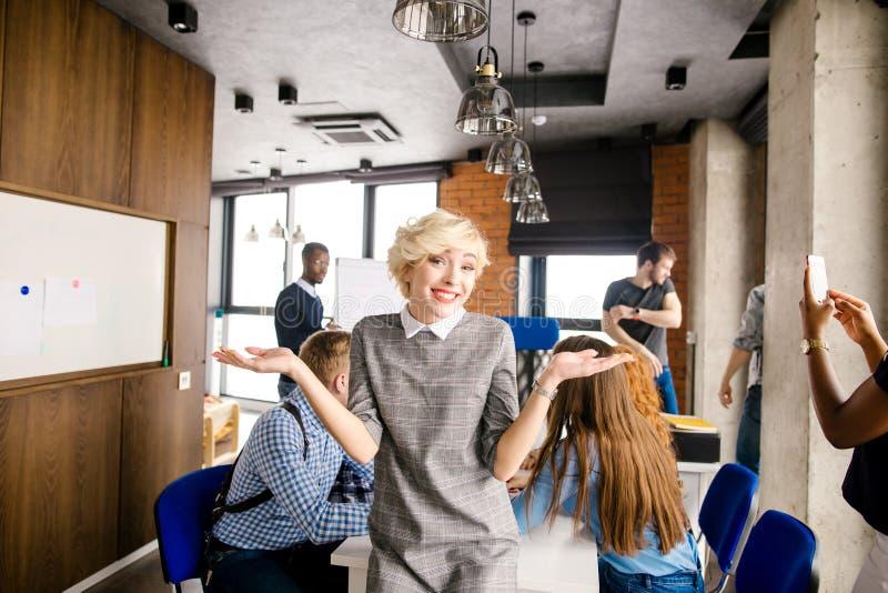 Femme d'entreprise positive avec les cheveux blonds courts portant la robe élégante images libres de droits