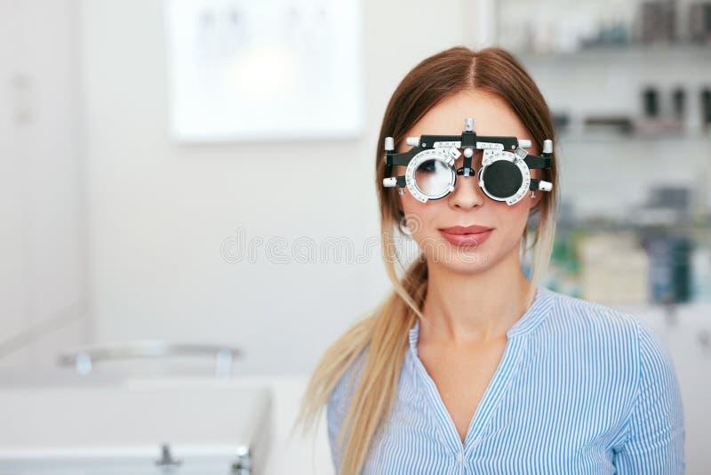 Femme d'essai de vue en optométrie de Trial Frame At d'optométriste photo stock