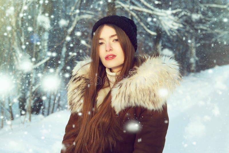 Femme d'hiver dans la neige regardant l'appareil-photo dehors le jour froid de chute de neige d'hiver Extérieur modèle femelle ca images libres de droits