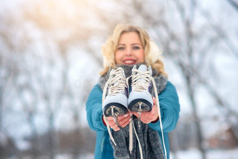 Femme d'hiver de patinage de glace de fille tenant des patins de glace dehors dans la neige photos libres de droits