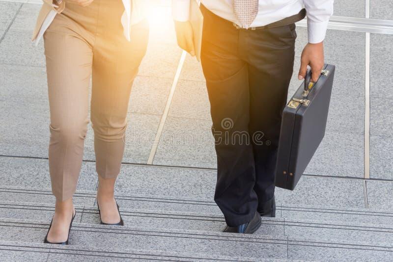 Femme d'homme d'affaires et d'affaires marchant vers le haut des escaliers avec des sacs photos libres de droits