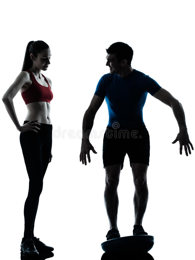 Femme d'homme d'entraîneur exerçant des postures accroupies sur la silhouette de bosu photographie stock