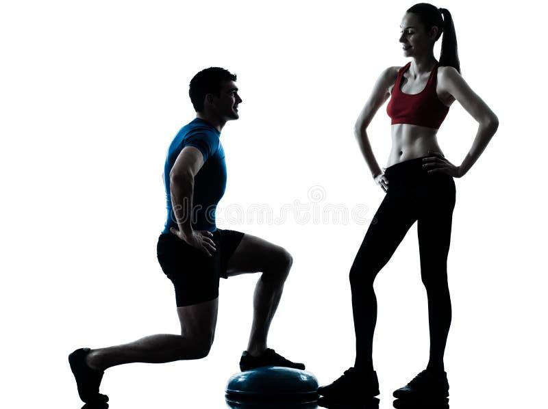 Femme d'homme d'entraîneur exerçant des postures accroupies sur la silhouette de bosu image stock