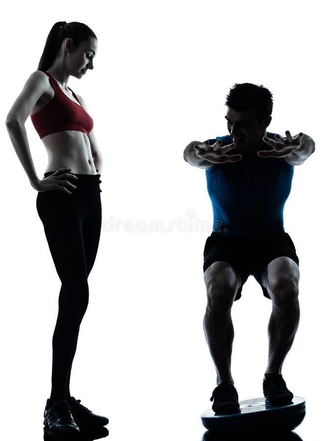 Femme d'homme d'entraîneur exerçant des postures accroupies sur le bosu photos libres de droits