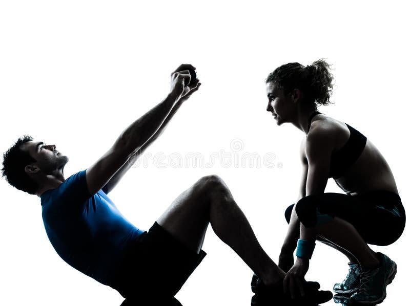 Femme d'homme exerçant la forme physique abdominale de séance d'entraînement image stock