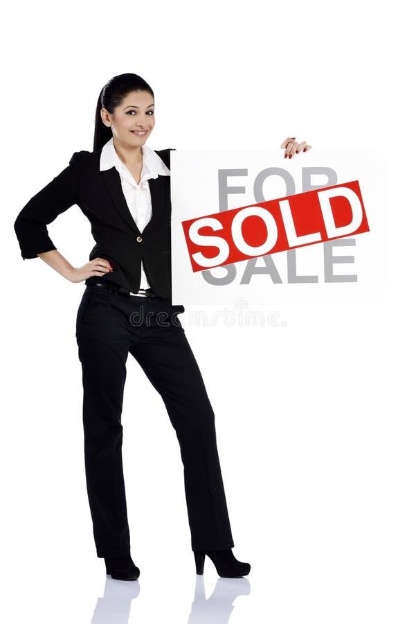 Femme d'immobiliers se tenant en vente - signe vendu photo stock
