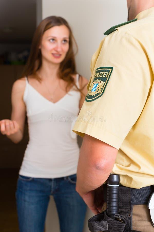 Femme d'interrogation de policier à l'entrée principale photographie stock libre de droits