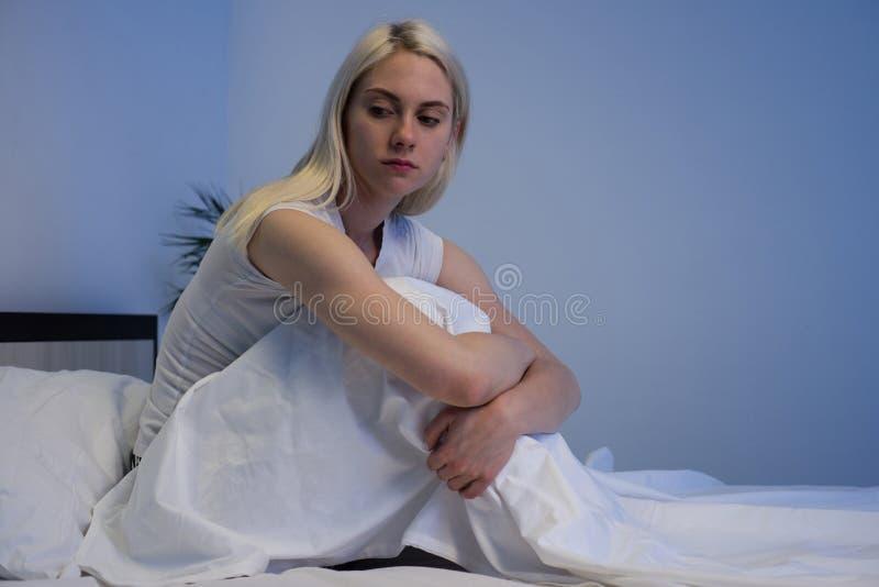 Femme d?prim?e triste s'asseyant dans son lit en retard la nuit, elle est songeuse et souffrante de l'insomnie images stock