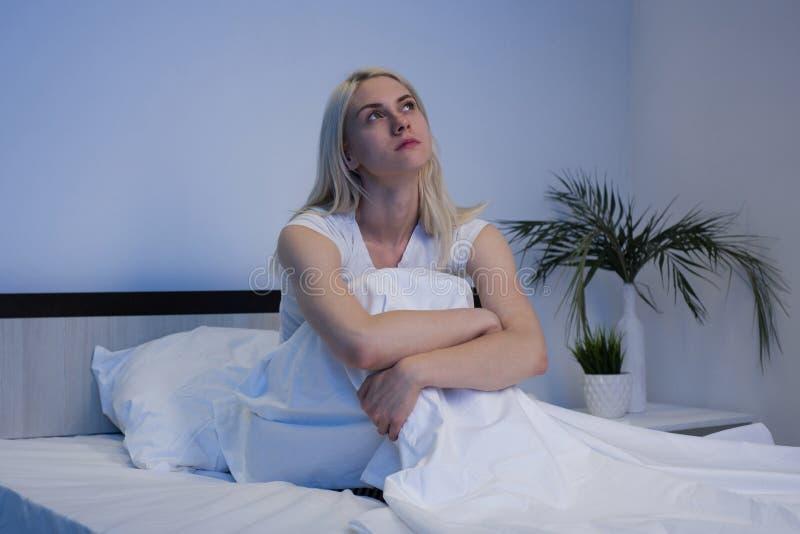 Femme d?prim?e triste s'asseyant dans son lit en retard la nuit, elle est songeuse et souffrante de l'insomnie photographie stock