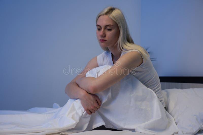 Femme d?prim?e triste s'asseyant dans son lit en retard la nuit, elle est songeuse et souffrante de l'insomnie photo libre de droits