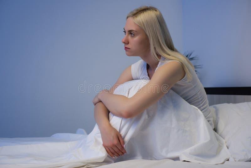 Femme d?prim?e triste s'asseyant dans son lit en retard la nuit, elle est songeuse et souffrante de l'insomnie photographie stock libre de droits