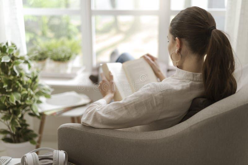 Femme d?tendant et lisant un livre images libres de droits