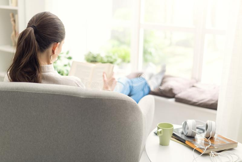 Femme d?tendant et lisant un livre photographie stock