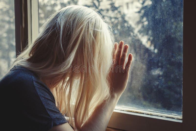 Femme d'une chevelure blonde se penchant contre la fenêtre, regardant, triste, déprimée et isolée avec de longs cheveux, photo libre de droits