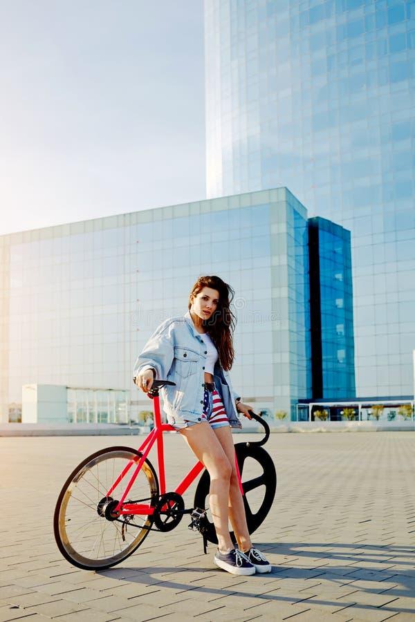 Femme d'une chevelure brune assez jeune se tenant avec sa bicyclette rose moderne dans la ville images stock