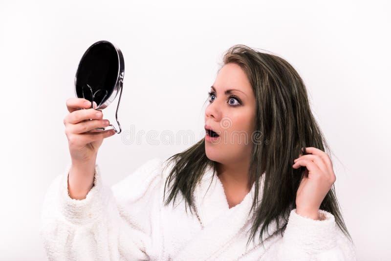 Femme d'une chevelure de Brown regardant choquée elle-même dans un miroir photographie stock