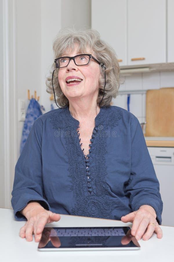 Femme d'une chevelure grise avec le touchpad photo stock