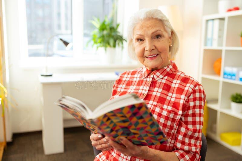 Femme d'une chevelure grise positive tenant un livre images libres de droits