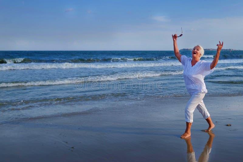 Femme d'une chevelure grise supérieure attirante dansant près du bord de mer photographie stock libre de droits