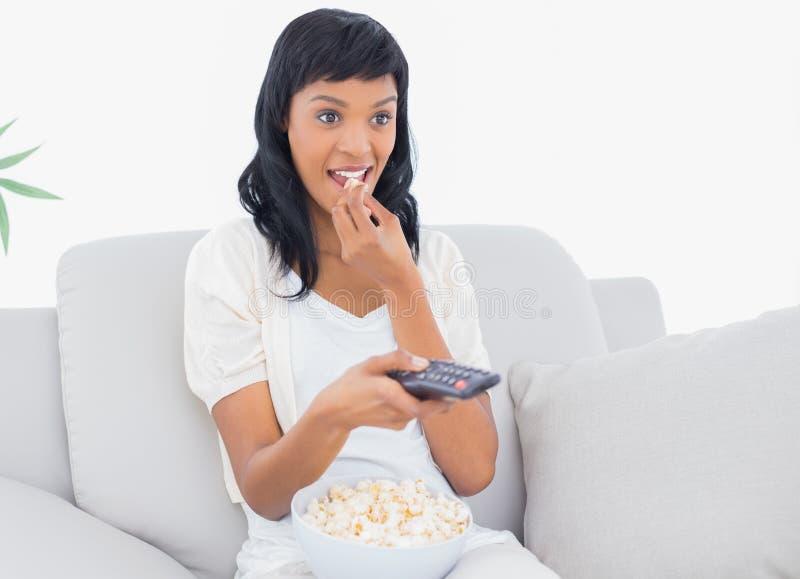 Femme d'une chevelure noire focalisée dans des vêtements blancs regardant la TV tout en mangeant du maïs éclaté image libre de droits