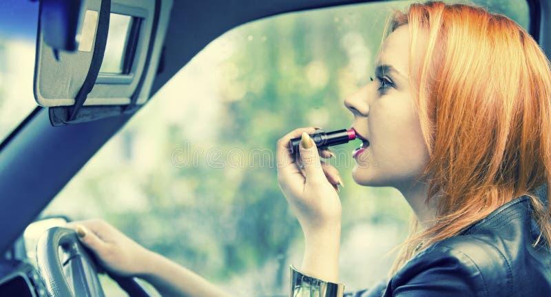 Femme d'une chevelure rouge appliquant le rouge à lèvres sur des lèvres dans la voiture. Danger sur la route. image stock