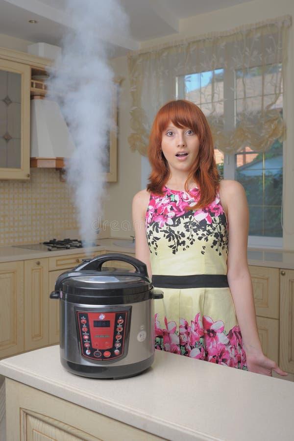 Femme d'une chevelure rouge avec le nouveau multicooker image libre de droits