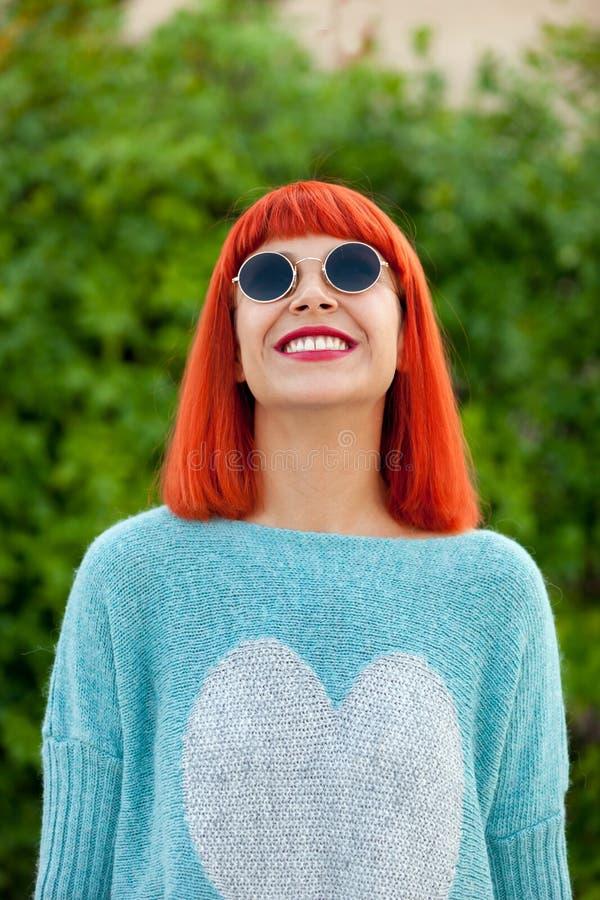 Femme d'une chevelure rouge avec les lunettes de soleil fraîches photographie stock