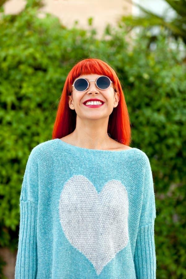 Femme d'une chevelure rouge avec les lunettes de soleil fraîches image libre de droits