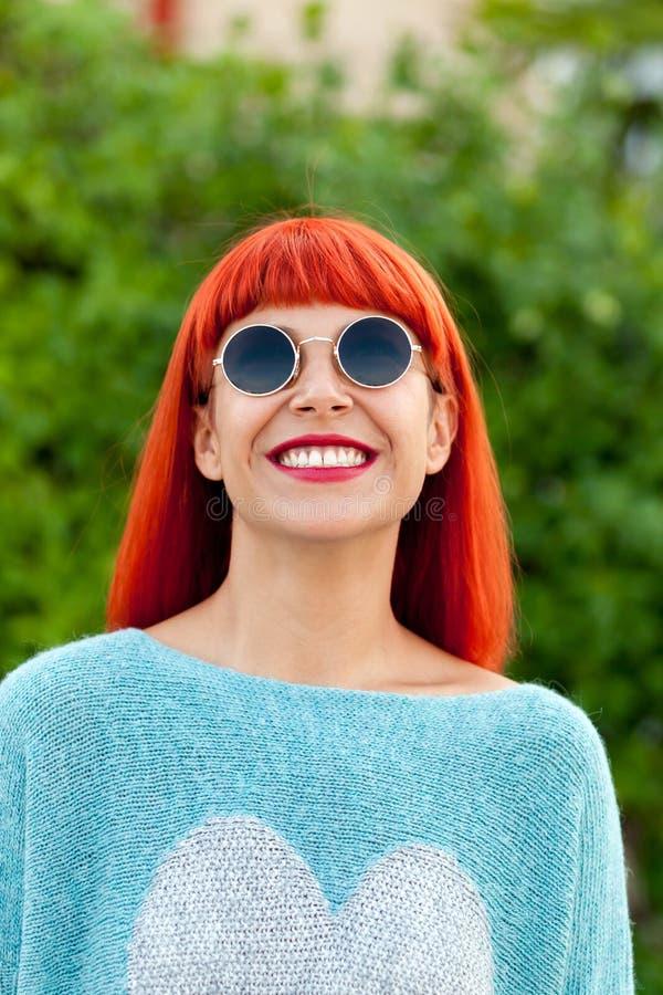 Femme d'une chevelure rouge avec les lunettes de soleil fraîches photo stock