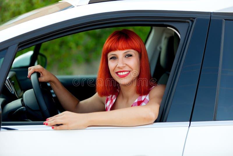Femme d'une chevelure rouge avec sa nouvelle voiture photo libre de droits